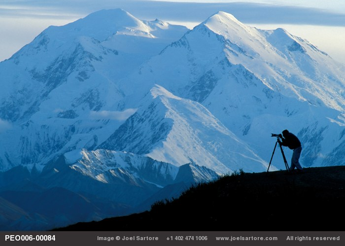 A hiker photographs the view of Mount McKinley in Alaska's Denali National Park.