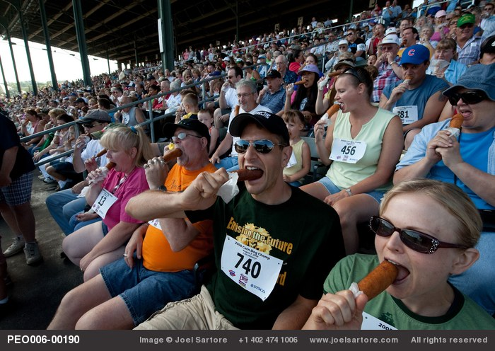 Iowa fairgoers bite in synchrony at the first-ever Corn Dog Chomp.